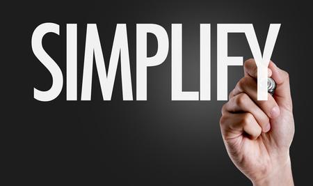 Hand schreibt das Wort: Simplify